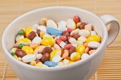 La taza blanca llenó de las píldoras de la medicina Imagenes de archivo