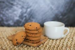 La taza blanca y las galletas de harina de avena hechas en casa doblaron en una pila en la placa de madera y el fondo gris Imagen de archivo libre de regalías