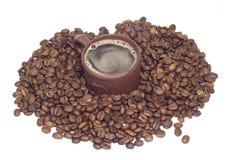 La taza con el coffe en granos de café aisló el onwhit Fotos de archivo libres de regalías