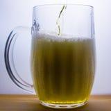 la taza con la cerveza ligera vierte Imágenes de archivo libres de regalías