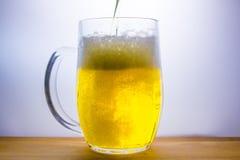 la taza con la cerveza ligera vierte Foto de archivo libre de regalías