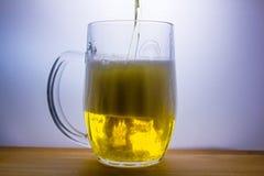 la taza con la cerveza ligera vierte Fotografía de archivo libre de regalías
