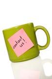 La taza con la nota nos entra en contacto con!. Imagenes de archivo