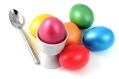 La taza con los huevos y la cuchara de Pascua en blanco aisló el fondo Imagen de archivo