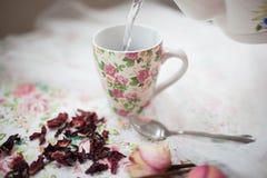 La taza con té rojo está en la tabla Imágenes de archivo libres de regalías