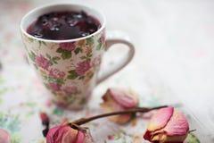 La taza con té rojo está en la tabla Fotografía de archivo