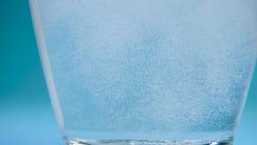 La taza de agua de cristal transparente cae la tableta del analgin almacen de video