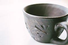 La taza de la arcilla se coloca en un fondo blanco fotos de archivo libres de regalías