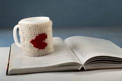 La taza de bebida caliente se coloca en el libro Imagen de archivo