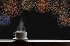 La taza de bebidas calientes en el escritorio de madera con Año Nuevo celebra los fuegos artificiales en el cielo nocturno Foto de archivo
