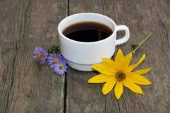 La taza de café adornó amarillo y azul con las flores Fotos de archivo