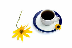 La taza de café adornó con dos flores del amarillo a la vida inmóvil Foto de archivo libre de regalías