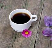 La taza de café adornada con una flor rosada y los pétalos de la lila Foto de archivo