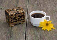 La taza de café adornada con una flor y un ataúd amarillos, sti Fotos de archivo