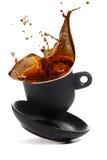La taza de café cae en la superficie blanca Foto de archivo libre de regalías