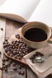 La taza de café caliente y el bosquejo blanco reservan en la tabla de madera Imágenes de archivo libres de regalías