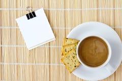 La taza de café caliente y el bosquejo blanco reservan en una estera Fotos de archivo libres de regalías