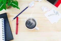 La taza de café con el smartphone, papel arrugado, vidrios, cuadernos, pluma, lápiz, clips de papel, verde deja el pote en el vin fotos de archivo