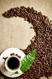 La taza de café con las habas torció en un remolino en la materia textil del lino Imagen de archivo