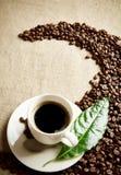 La taza de café con las habas torció en un remolino en la materia textil del lino Imagenes de archivo
