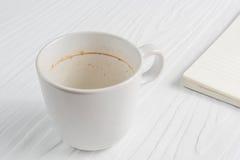 La taza de café con las manchas del café no ha lavado la taza colocada en la tabla blanca Foto de archivo libre de regalías