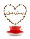 La taza de café con los granos de café formó el corazón con la muestra de la buena mañana Fotos de archivo libres de regalías