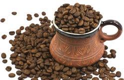 La taza de café de cerámica de Brown llenó de los granos de café Foto de archivo
