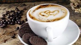 La taza de café del latte con leche puso una tabla de madera con los granos de café asados oscuridad Foto de archivo