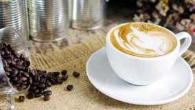 La taza de café del latte, del capuchino o del café express con leche puso una tabla de madera con los granos de café asados oscu Foto de archivo