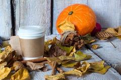 La taza de café disponible con amarillo del otoño se va en fondo de madera del fondo Concepto de la estación del otoño Imagenes de archivo