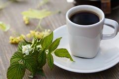 La taza de café, el pote del café y el tilo florecen en la tabla Imagen de archivo libre de regalías