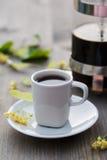 La taza de café, el pote del café y el tilo florecen en la tabla Foto de archivo libre de regalías