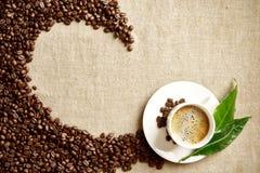 La taza de café espumosa, habas, hoja torció en remolino en el lino Imagenes de archivo