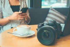 La taza de café está en la tabla cerca de cámara y de ordenador portátil imagenes de archivo