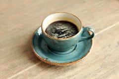 La taza de café incompleta está en la tabla Fotos de archivo libres de regalías