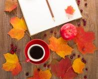 La taza de café, libreta, manzanas, haciendo punto, hojas de otoño Foto de archivo libre de regalías