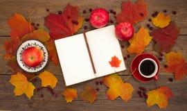 La taza de café, libreta, manzanas, haciendo punto, hojas de otoño Imagen de archivo libre de regalías
