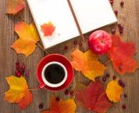 La taza de café, libreta, manzanas, hojas de otoño Imágenes de archivo libres de regalías