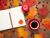 La taza de café, libreta, manzanas, hojas de otoño Fotografía de archivo