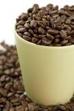 La taza de café llenó de los granos de café Imagen de archivo
