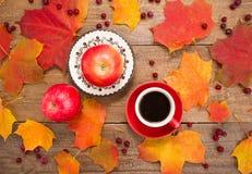 La taza de café, manzanas, hojas de otoño Fotografía de archivo libre de regalías