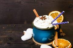 La taza de café de la Navidad con la crema azotada, canela, polvo de cacao, anís, secó las galletas de la naranja y del pan de je fotografía de archivo