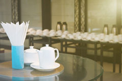 La taza de café o una taza de té con una tetera o un cuenco y un papel seda de la leche se coloca en una tabla de cristal para el Fotos de archivo libres de regalías