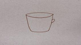 La taza de café pintada por el rotulador marrón en la cartulina, dibujo simple, para la animación del movimiento metrajes