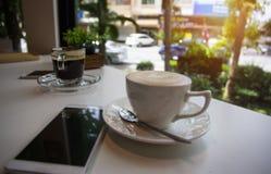 La taza de café puso al lado del teléfono del moblie, en la cafetería fotografía de archivo