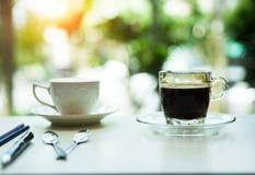 La taza de café puso la tabla, fondo ligero borroso del diseño fotos de archivo libres de regalías