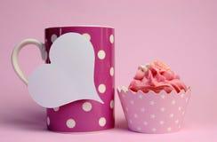 La taza de café rosada del lunar con la magdalena rosada y el corazón blanco en blanco forman la etiqueta del regalo Imágenes de archivo libres de regalías