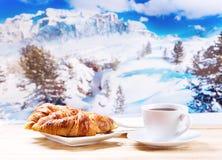 La taza de café y los cruasanes durante invierno ajardinan Imágenes de archivo libres de regalías