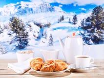 La taza de café y los cruasanes durante invierno ajardinan Imagenes de archivo