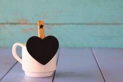 La taza de café y poco corazón forman la pizarra Fotografía de archivo